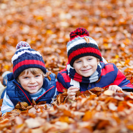 Two little kid boys lying in autumn leaves, in park.