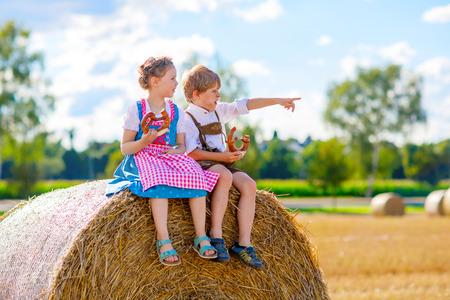 Zwei Kinder, Junge und Mädchen in traditionellen bayerischen Kostümen im Weizenfeld Standard-Bild - 84622270