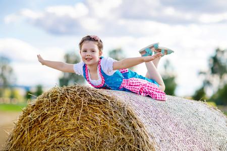 Nettes kleines Mädchen im traditionellen bayerischen Kostüm im Weizenfeld Standard-Bild - 84621865