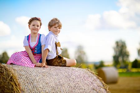 2 人の子供、男の子と女の子に麦畑の伝統的なバイエルンの衣装 写真素材