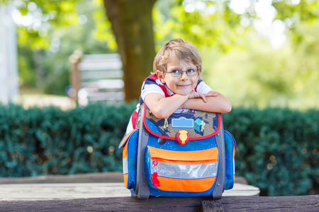 Happy little kid boy with glasses and backpack or satchel on his first day to school . Child outdoors on warm sunny day, Back to school concept. Kid with traditional schoolbag in German Schultuete Stock Photo