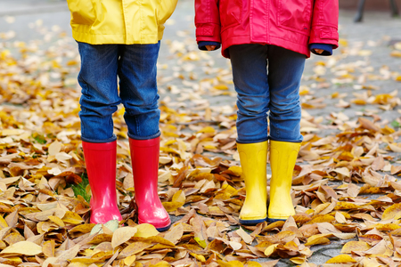 kiddies: Closeup of kids legs in rubber boots dancing and walking through fall leaves