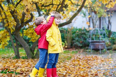 Due piccoli amici e ragazzi ragazzi autunno parco in colorato cl Archivio Fotografico - 84622192