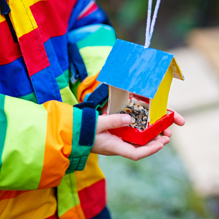 Little kid hanging bird house on tree for feeding in winter