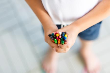 Childs handen met veel kleurrijke waskrijtjes Stockfoto - 85042071