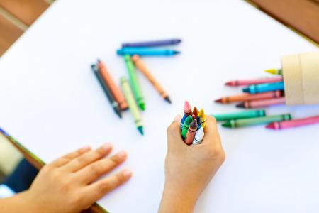Childs handen met veel kleurrijke waskrijtjes