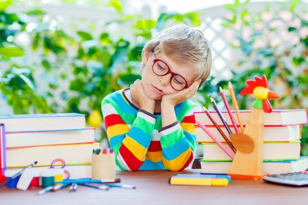 Sad school kid boy with glasses and student stuff Stock Photo
