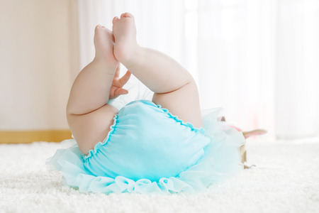 nude little girls: Close-up of legs and feet of baby girl on white background wearing turquoise tutu skirt. Stock Photo