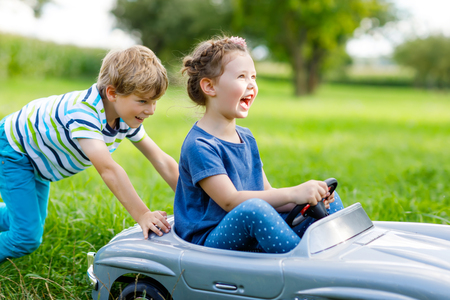 Two happy children boy and girl playing with big old toy car in summer garden, outdoors Stock Photo