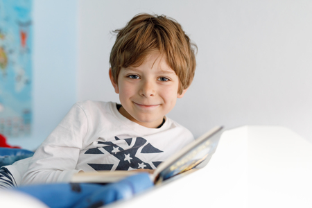 Cute blond little kid boy in pajamas reading book in his bedroom