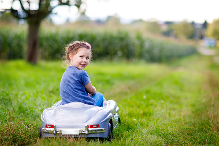 Little preschool kid girl sitting on old big toy car and having fun on sunny summer day Stock Photo