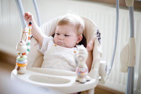 Cute adorable newborn baby girl sitting in swing indoors