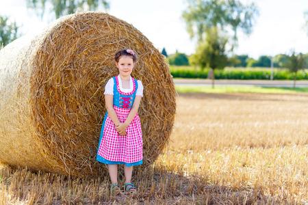 Nettes kleines Mädchen im traditionellen bayerischen Kostüm im Weizenfeld Standard-Bild - 85164103