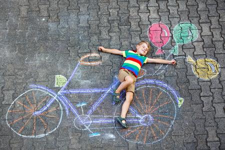 klein kind jongen met plezier met fiets krijtjes foto op de grond Stockfoto