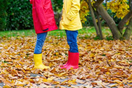 Closeup of kids legs in rubber boots dancing and walking through fall leaves