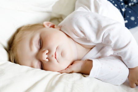 swaddling: Cute adorable baby girl of 6 months sleeping peaceful in bed