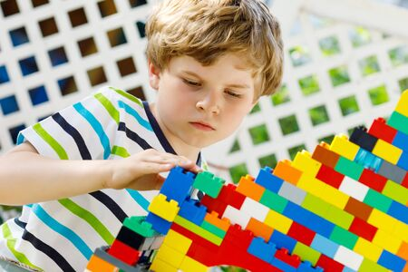 Little blond child and kid boy playing with lots of colorful plastic blocks.