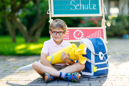 Happy little kid boy with glasses sitting by desk and backpack or satchel