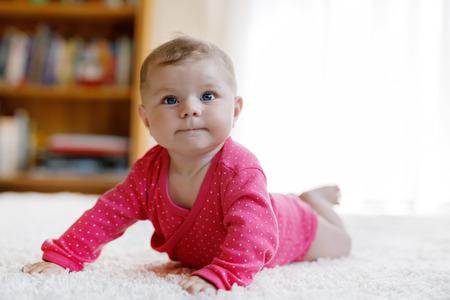 Portret van kleine kleine babymeisje van 5 maanden binnen thuis