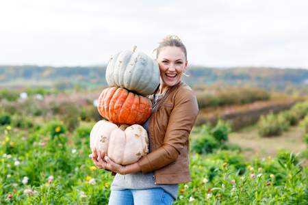 Beautiful woman with three huge pumpkins on farm