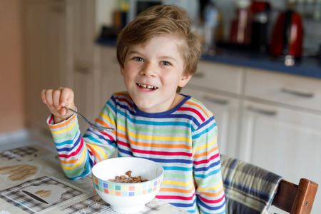 아침이나 점심에 대 한 시리얼을 먹고 행복 작은 금발 아이 소년. 어린이를위한 건강한 식생활.