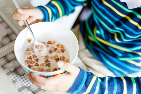 Closeup of hands of kid boy eating homemade cereals for breakfast or lunch Stock Photo