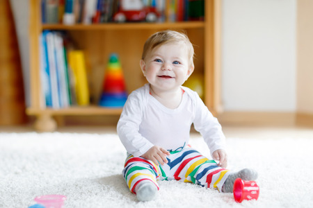 Adorable baby girl playing with educational toys in nursery
