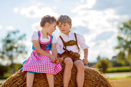 Two kids, boy and girl in traditional Bavarian costumes in wheat field 写真素材