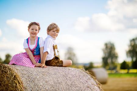 Zwei Kinder, Junge und Mädchen in den traditionellen bayerischen Kostümen auf dem Weizengebiet Standard-Bild - 86362765