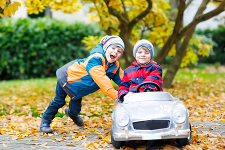 Two happy twins kids boys having fun and playing with big old toy car in autumn garden