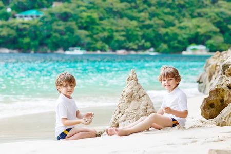Twee jong geitjejongens die zandkasteel bouwen op tropisch strand