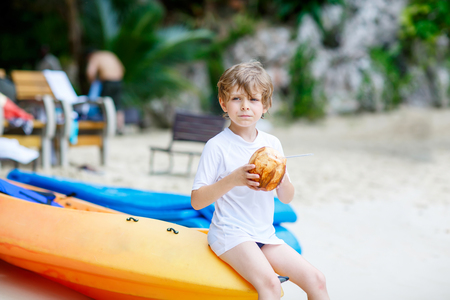 Little kid boy drinking coconut juice on tropical beach