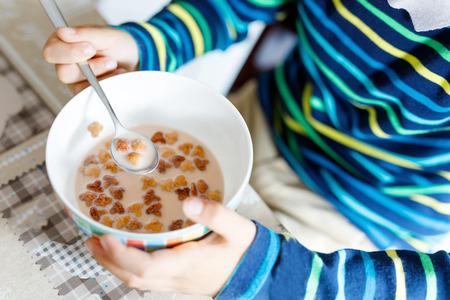 comedor escolar: Closeup of hands of kid boy eating homemade cereals for breakfast or lunch Foto de archivo