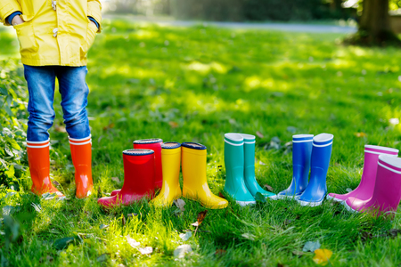 Little kid, boy or girl in jeans and yellow jacket in colorful rain boots.