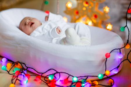One week old newborn baby girl sleeping near Christmas tree