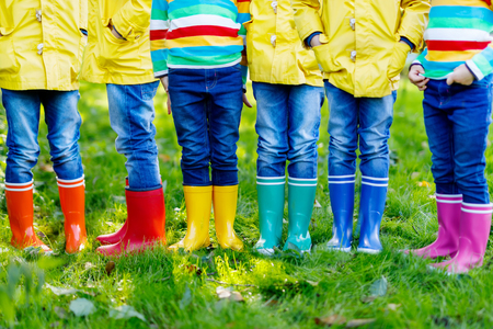 Little kids, boys or girls in jeans and yellow jacket in colorful rain boots Reklamní fotografie