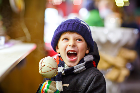 dresden: Little kid boy eating sugar apple sweets stand on Christmas market