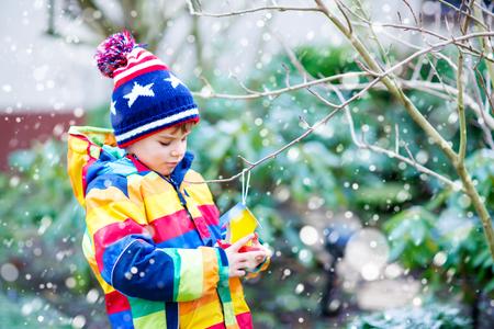 冬の給餌のための木の鳥の家をぶら下げ子供男の子
