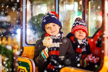Two little kids boys on carousel at Christmas market