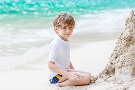 Little kid boy building sand castle on tropical beach