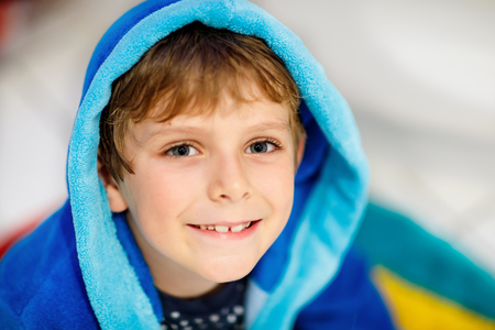 Portrait of beautiful smiling kid boy. Happy child in blue bathrobe