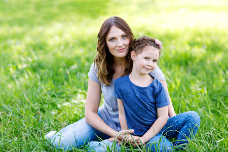 Beautiful young mother and little daughter sitting on green grass and resting Banco de Imagens