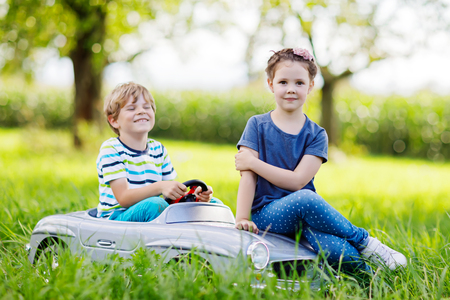 cute guy: Two happy children playing with big old toy car in summer garden, outdoor