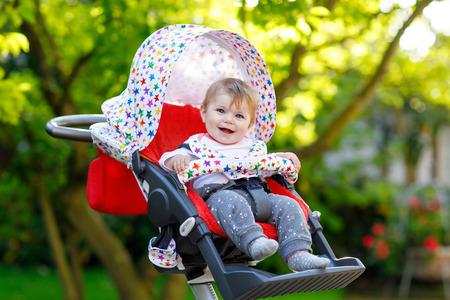 ベビーシッターやベビーカーに座ってママを待っている6ヶ月のかわいい小さな美しい女の子 写真素材