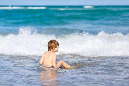 little blond kid boy having fun on ocean beach in Florida Stock Photo