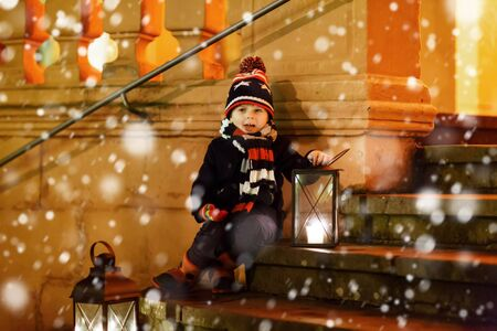 tradition: Little cute kid boy with with a light lantern on stairs near church. Stock Photo