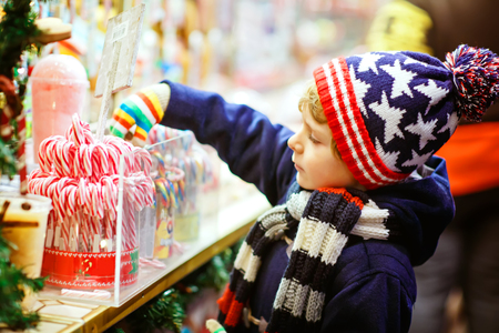 Little cute kid boy buying sweets from a cancy stand on Christmas market Stock Photo