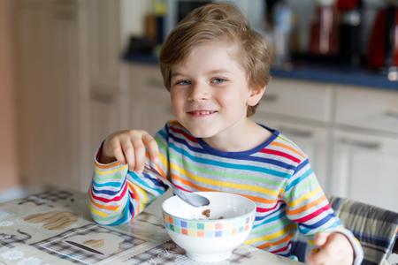 comedor escolar: Happy little blond kid boy eating cereals for breakfast or lunch. Healthy eating for children. Foto de archivo
