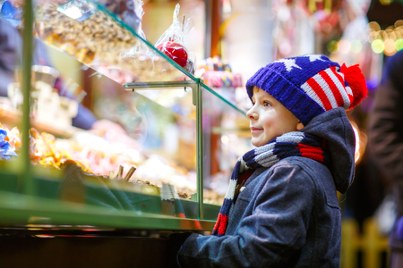 dresden: Little kid boy with gingerbread and sweets stand on Christmas market
