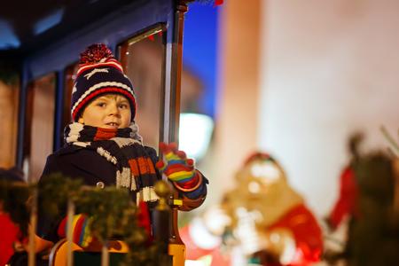 Little kid boy on carousel at Christmas market